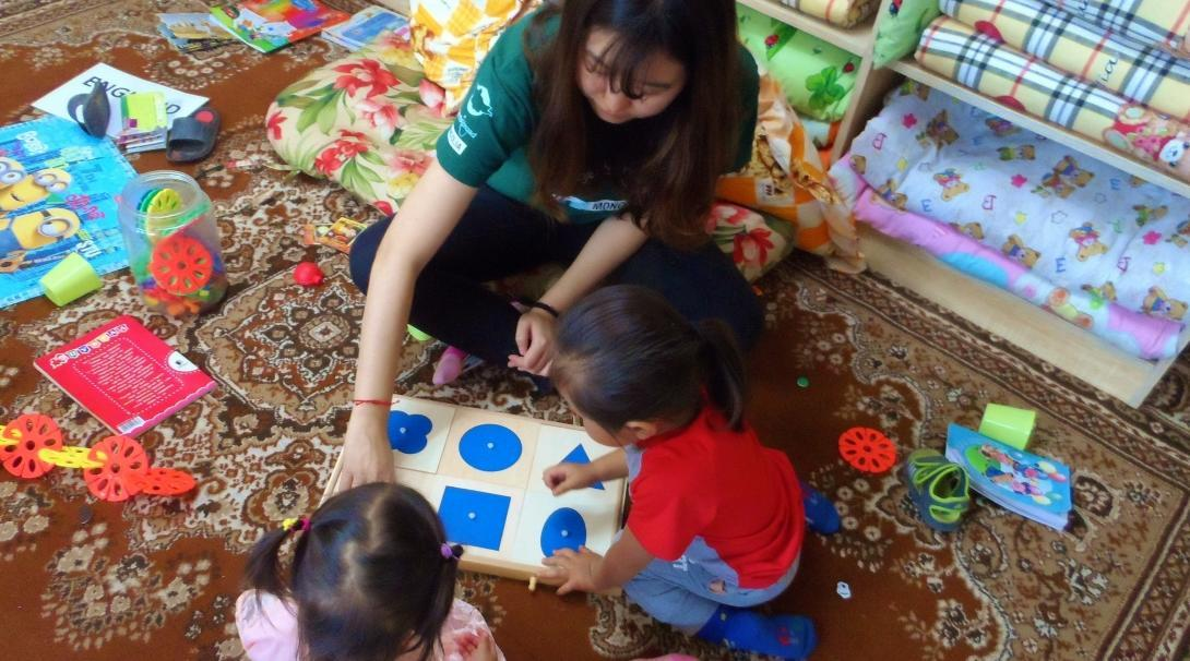 Projects Abroad Childcare volunteer teaches children shape games in a care centre during a Psychology work experience in Mongolia.
